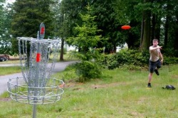 Man throwing a red frisbee into a silver, metal disc golf net