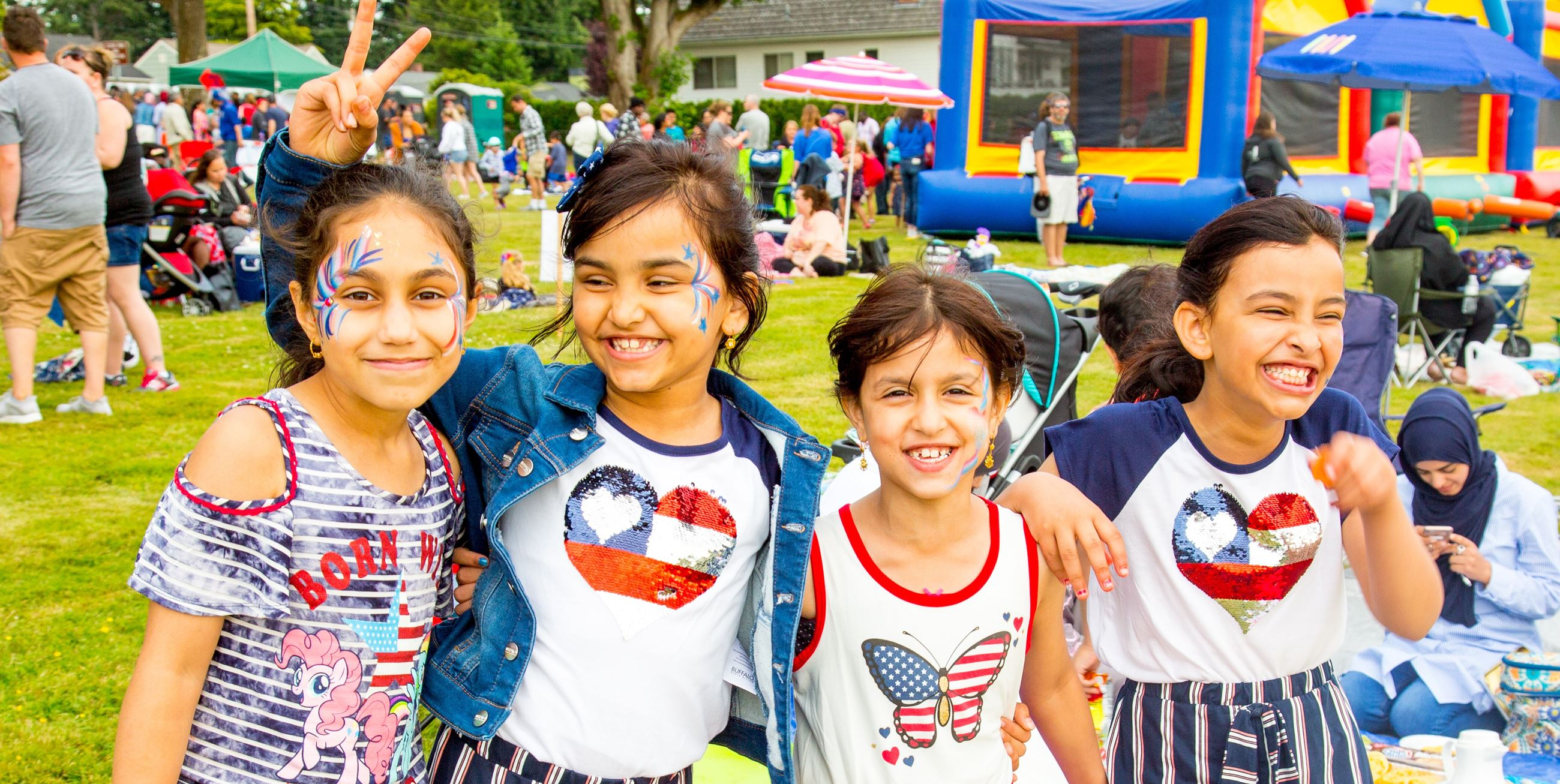 Four school-age girls standing together smiling in front of a bouncy house