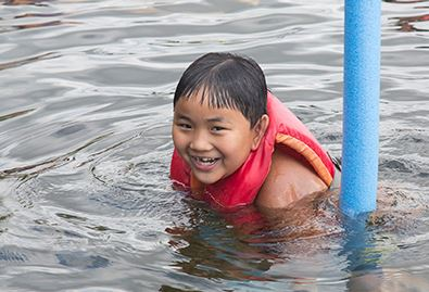 Child Swimming in a Life Jacket