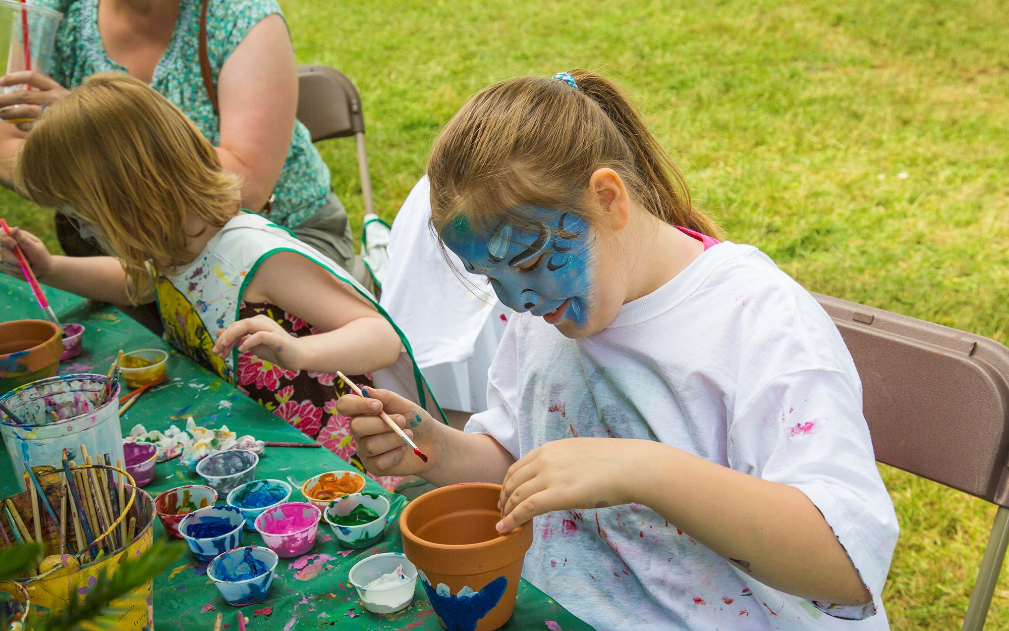 Girl with her face painted, painting a planter pot